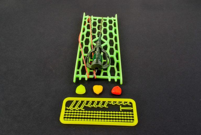 MAD CARP. Zestaw Method Classic Mały 13 gr. na kulkę proteinową nr 1.Składa się on z plecionki przyponowej złożonej się ze splotu 16 specjalnych włókien o długości ok. 60 cm , przyponu o długości ok. 16 cm ,zasobnika na zanętę 3D o wadze 13 gram , dwóch krętlików , stopera i haczyka z włosem. Dzięki unikalnej konstrukcji koszyka zanętowego 3D w połączeniu z asymetrycznym ciężarkiem oraz zastosowaniu specjalnych wypustek na górnym ramieniu  – wskazujących gdzie wbić haczyk – zawsze wiemy w jakiej pozycji zestaw ustawi się na dnie zbiornika wodnego. Ponadto konstrukcja 3D doskonale utrzyma zanętę , podczas zarzucania zestawu.  Specjalna konstrukcja powoduje , że ryba po połknięciu haczyka początkowo nie czuje oporu i nie odrzuca połkniętej przynęty. Koszyk zanętowy zbudowany jest z doskonałej jakości plastiku oraz ciężarka z ołowiu pomalowanego farbą proszkową . Najwyższej jakości koreański haczyk , wyprodukowany na nasze specjalne zamówienie z japońskiej , hartowanej , wysokowęglowej  stali , nie zawiedzie przy holowaniu nawet największych okazów ryb. Pokryty teflonem gwarantuje bezrefleksyjność w środowisku wodnym, oraz wyższą odporność na korozję. Zastosowano plecionkę przyponową o wytrzymałości 45 lbs (20,41 kg), przypon 30lbs ( 13,60 kg ).  Całość zamocowana na odpowiednim stelażu , uniemożliwiającym splątanie zestawu.