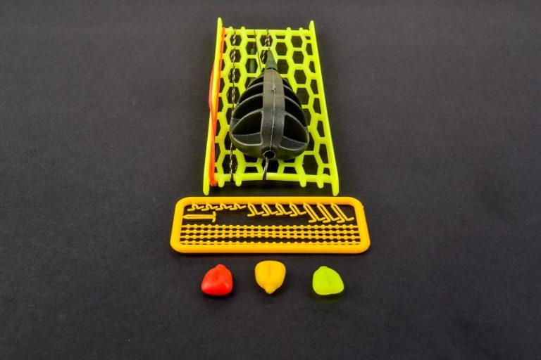 """MAD CARP. Zestaw Method Feeder nr 2 65gr. na kulkę Proteinową №1. Dzięki konstrukcji """" koszyka zanętowego"""" , zawsze wiemy w jakiej pozycji zestaw ustawi się na dnie zbiornika wodnego.  Składa się on z plecionki przyponowej złożonej się ze splotu 16 specjalnych włókien o długości ok. 60 cm , przyponu o długości ok. 16 cm , zasobnika na zanętę o wadze 45 gram, dwóch  krętlików , stopera i haczyka z włosem. Specjalna konstrukcja powoduje , że ryba po połknięciu haczyka początkowo nie czuje oporu i nie odrzuca połkniętej przynęty. Koszyk zanętowy zbudowany jest z doskonałej jakości plastiku oraz zalanego w nim metalu dociążającego .  Najwyższej jakości koreański haczyk , wyprodukowany na nasze specjalne zamówienie z japońskiej , hartowanej , wysokowęglowej  stali , nie zawiedzie przy holowaniu nawet największych okazów ryb. Pokryty teflonem gwarantuje bezrefleksyjność w środowisku wodnym, oraz wyższą odporność na korozję . Zastosowano plecionkę przyponową o wytrzymałości 45 lbs (20,41 kg), przypon 30lbs ( 13,60 kg ).  Całość zamocowana na odpowiednim stelażu , uniemożliwiającym splątanie zestawu ."""