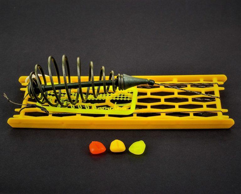 MAD CARP. Zestaw Sprężyna lekka zielona nr 1. Składa się on z plecionki przyponowej złożonej się ze splotu 16 specjalnych włókien o długości ok. 60 cm , przyponu o długości ok. 16 cm , sprężyny na zanętę , dwóch  krętlików , stopera i haczyka z włosem. Specjalna konstrukcja powoduje , że ryba po połknięciu haczyka początkowo nie czuje oporu i nie odrzuca połkniętej przynęty. Sprężyna zbudowana jest z doskonałej jakości stali . Części metalowe zestawu pomalowane są farbą proszkową . Najwyższej jakości koreański haczyk , wyprodukowany na nasze specjalne zamówienie z japońskiej , hartowanej , wysokowęglowej  stali , nie zawiedzie przy holowaniu nawet największych okazów ryb. Pokryty teflonem gwarantuje bezrefleksyjność w środowisku wodnym, oraz wyższą odporność na korozję . Zastosowano plecionkę przyponową o wytrzymałości 45 lbs (20,41 kg), przypon 30lbs ( 13,60 kg ).  Całość zamocowana na odpowiednim stelażu , uniemożliwiającym splątanie zestawu.