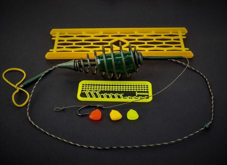 MAD CARP    Zestaw Sprężyna z obciążeniem zielona 120gr. na kulkę proteinową nr 1. Składa się on z plecionki przyponowej złożonej się ze splotu 16 specjalnych włókien o długości ok. 60 cm , przyponu o długości ok. 16 cm , sprężyny na zanętę o wadze 60 gram , dwóch  krętlików , stopera i haczyka z włosem. Specjalna konstrukcja powoduje , że ryba po połknięciu haczyka początkowo nie czuje oporu i nie odrzuca połkniętej przynęty. Sprężyna zbudowana jest z doskonałej jakości stali oraz ciężarka z ołowiu. Części metalowe zestawu pomalowane są farbą proszkową . Najwyższej jakości koreański haczyk , wyprodukowany na nasze specjalne zamówienie z japońskiej , hartowanej , wysokowęglowej  stali , nie zawiedzie przy holowaniu nawet największych okazów ryb. Pokryty teflonem gwarantuje bezrefleksyjność w środowisku wodnym, oraz wyższą odporność na korozję . Zastosowano plecionkę przyponową o wytrzymałości 45 lbs (20,41 kg), przypon 30lbs ( 13,60 kg ).  Całość zamocowana na odpowiednim stelażu , uniemożliwiającym splątanie zestawu.