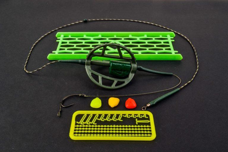 MAD CARP. Zestaw Method Classic Duży 35 gr. na kulkę Proteinową №1. Składa się on z plecionki przyponowej złożonej się ze splotu 16 specjalnych włókien o długości ok. 60 cm , przyponu o długości ok. 16 cm ,zasobnika na zanętę 3D o wadze 95 gram, dwóch krętlików , stopera i haczyka z włosem. Dzięki unikalnej konstrukcji koszyka zanętowego 3D w połączeniu z asymetrycznym ciężarkiem oraz zastosowaniu specjalnych wypustek na górnym ramieniu  – wskazujących gdzie wbić haczyk – zawsze wiemy w jakiej pozycji zestaw ustawi się na dnie zbiornika wodnego. Ponadto konstrukcja 3D doskonale utrzyma zanętę , podczas zarzucania zestawu.  Specjalna konstrukcja powoduje , że ryba po połknięciu haczyka początkowo nie czuje oporu i nie odrzuca połkniętej przynęty. Koszyk zanętowy zbudowany jest z doskonałej jakości plastiku oraz ciężarka z ołowiu pomalowanego farbą proszkową . Najwyższej jakości koreański haczyk , wyprodukowany na nasze specjalne zamówienie z japońskiej , hartowanej , wysokowęglowej  stali , nie zawiedzie przy holowaniu nawet największych okazów ryb. Pokryty teflonem gwarantuje bezrefleksyjność w środowisku wodnym, oraz wyższą odporność na korozję. Zastosowano plecionkę przyponową o wytrzymałości 45 lbs (20,41 kg), przypon 30lbs ( 13,60 kg ).  Całość zamocowana na odpowiednim stelażu , uniemożliwiającym splątanie zestawu.