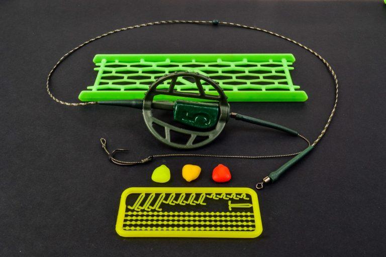 MAD CARP. Zestaw Method Classic Duży 45 gr. na kulkę Proteinową №1. Składa się on z plecionki przyponowej złożonej się ze splotu 16 specjalnych włókien o długości ok. 60 cm , przyponu o długości ok. 16 cm ,zasobnika na zanętę 3D o wadze 95 gram, dwóch krętlików , stopera i haczyka z włosem. Dzięki unikalnej konstrukcji koszyka zanętowego 3D w połączeniu z asymetrycznym ciężarkiem oraz zastosowaniu specjalnych wypustek na górnym ramieniu  – wskazujących gdzie wbić haczyk – zawsze wiemy w jakiej pozycji zestaw ustawi się na dnie zbiornika wodnego. Ponadto konstrukcja 3D doskonale utrzyma zanętę , podczas zarzucania zestawu.  Specjalna konstrukcja powoduje , że ryba po połknięciu haczyka początkowo nie czuje oporu i nie odrzuca połkniętej przynęty. Koszyk zanętowy zbudowany jest z doskonałej jakości plastiku oraz ciężarka z ołowiu pomalowanego farbą proszkową . Najwyższej jakości koreański haczyk , wyprodukowany na nasze specjalne zamówienie z japońskiej , hartowanej , wysokowęglowej  stali , nie zawiedzie przy holowaniu nawet największych okazów ryb. Pokryty teflonem gwarantuje bezrefleksyjność w środowisku wodnym, oraz wyższą odporność na korozję. Zastosowano plecionkę przyponową o wytrzymałości 45 lbs (20,41 kg), przypon 30lbs ( 13,60 kg ).  Całość zamocowana na odpowiednim stelażu , uniemożliwiającym splątanie zestawu.