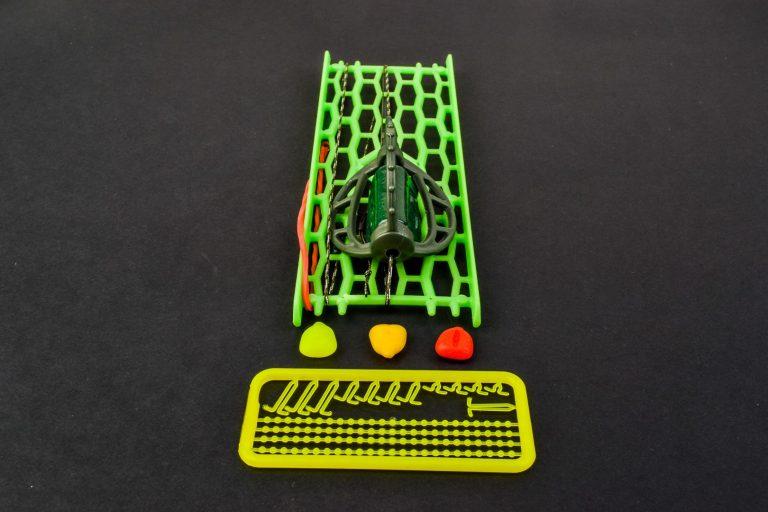 MAD CARP.  Zestaw Method Classic Średni 55 gr. na kulkę proteinową nr 1. Składa się on z plecionki przyponowej złożonej się ze splotu 16 specjalnych włókien o długości ok. 60 cm , przyponu o długości ok. 16 cm ,zasobnika na zanętę 3D o wadze 55 gram, dwóch krętlików , stopera i haczyka z włosem. Dzięki unikalnej konstrukcji koszyka zanętowego 3D w połączeniu z asymetrycznym ciężarkiem oraz zastosowaniu specjalnych wypustek na górnym ramieniu  – wskazujących gdzie wbić haczyk – zawsze wiemy w jakiej pozycji zestaw ustawi się na dnie zbiornika wodnego. Ponadto konstrukcja 3D doskonale utrzyma zanętę , podczas zarzucania zestawu.  Specjalna konstrukcja powoduje , że ryba po połknięciu haczyka początkowo nie czuje oporu i nie odrzuca połkniętej przynęty. Koszyk zanętowy zbudowany jest z doskonałej jakości plastiku oraz ciężarka z ołowiu pomalowanego farbą proszkową . Najwyższej jakości koreański haczyk , wyprodukowany na nasze specjalne zamówienie z japońskiej , hartowanej , wysokowęglowej  stali , nie zawiedzie przy holowaniu nawet największych okazów ryb. Pokryty teflonem gwarantuje bezrefleksyjność w środowisku wodnym, oraz wyższą odporność na korozję. Zastosowano plecionkę przyponową o wytrzymałości 45 lbs (20,41 kg), przypon 30lbs ( 13,60 kg ).  Całość zamocowana na odpowiednim stelażu , uniemożliwiającym splątanie zestawu.