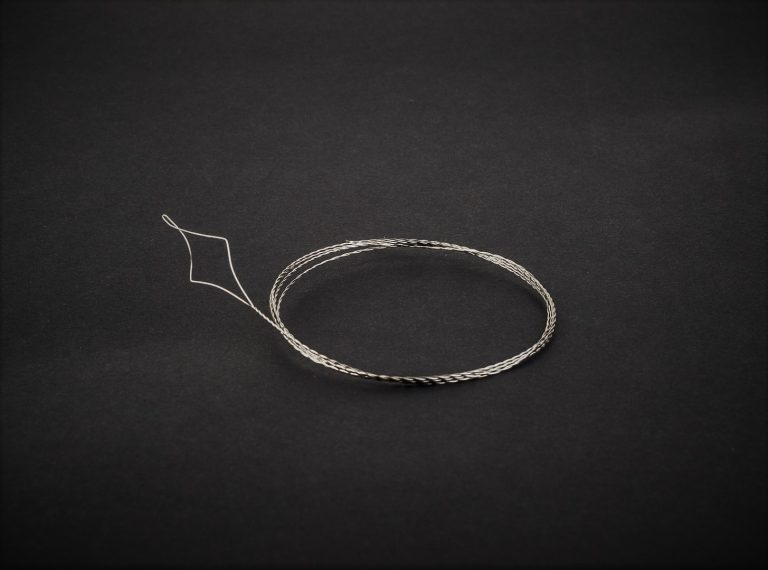 MAD CARP  Przyrząd do przewlekania żyłki (stalowy).Wymiary ok. 75 cm , wykonany z bardzo cienkiego , nierdzewnego drutu o średnicy 0,1mm. Przydatny do przewlekania żyłek i plecionek przez rurkę antysplątaniową.