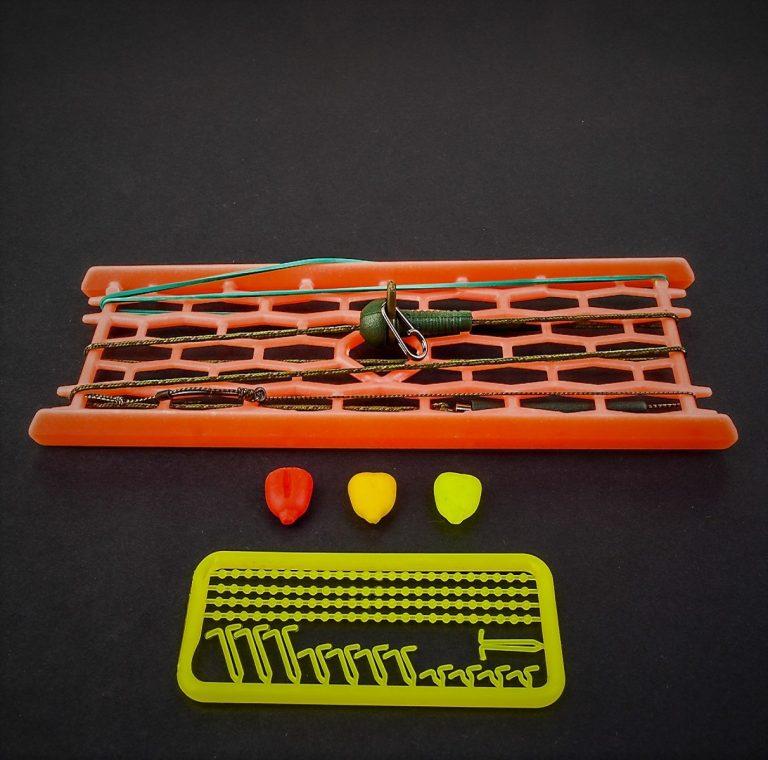MAD CARP  Zestaw karpiowy z lead core Nr.2 Zestaw przelotowy, składa się on z leadcore  praktycznie niewidocznym  na ciemnym i mulistym dnie, o długości  ok. 60 cm,  który doskonale układa się na dnie i jest odporny na ścieranie. Najwyższej jakości kuty koreański haczyk , wyprodukowany na nasze specjalne zamówienie z japońskiej , hartowanej , wysokowęglowej  stali , nie zawiedzie przy holowaniu nawet największych okazów ryb. Pokryty teflonem gwarantuje bezrefleksyjność w środowisku wodnym, oraz wyższą odporność na korozję . Zestaw uzbrojony w tulejkę z agrafkę do szybkiej ciężarka  Zastosowano leadcore o wytrzymałości 45 lbs (20,41 kg), przypon 30lbs ( 13,60 kg ).  Całość zamocowana na odpowiednim stelażu , uniemożliwiającym splątanie zestawu.